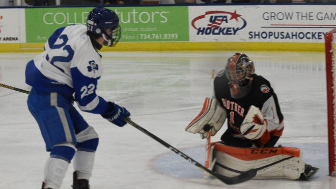 Brother Rice goalie Pierce Cadieux makes a save on Catholic Central's Dylan Montie in an MIHL game played earlier this year.