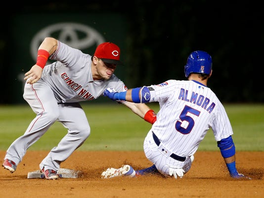 Cincinnati Reds second baseman Scooter Gennett tags out Chicago Cubs' Albert Almora Jr. after Almora Jr. tried to stretch his hit to a double during the seventh inning of a baseball game Tuesday, Aug. 15, 2017, in Chicago. (AP Photo/Charles Rex Arbogast)