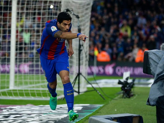 "FILE - In this April 5, 2017 file photo, FC Barcelona's Luis Suarez reacts in front of a TV camera after scoring during the Spanish La Liga soccer match against Sevilla at the Camp Nou stadium in Barcelona, Spain. La Liga is sending a clear message that it will not allow piracy to get in the way of its fight with the Premier League as it needs every possible source of income to try to compete financially with the powerful English league. It resorts to a proprietary tool to monitor the internet and uses a group of ""online guards"" to denounce illegal broadcasts of games. (AP Photo/Manu Fernandez, File)"