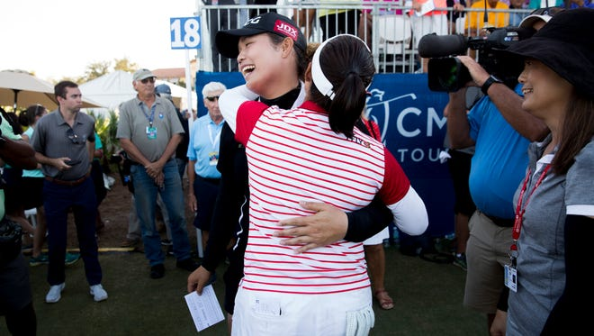 LPGA Tour pro Ariya Jutanugarn is embraced by her sister and fellow pro Moriya Jutanugarn after sinking a birdie putt on the 18th hole to claim outright victory during the final round of the CME Group Tour Championship at Tiburón Golf Club on Sunday. Jutanugarn won the tournament with a score of 15 under.