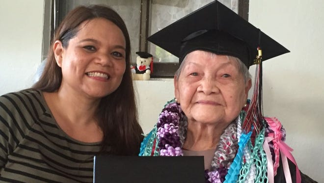 World War II survivor Guadalupe S. Perez, 90, right, receives her honorary Simon Sanchez High School diploma at her family's Yigo home Tuesday, May 31. With her is her grandchild Arnell F. Medler.