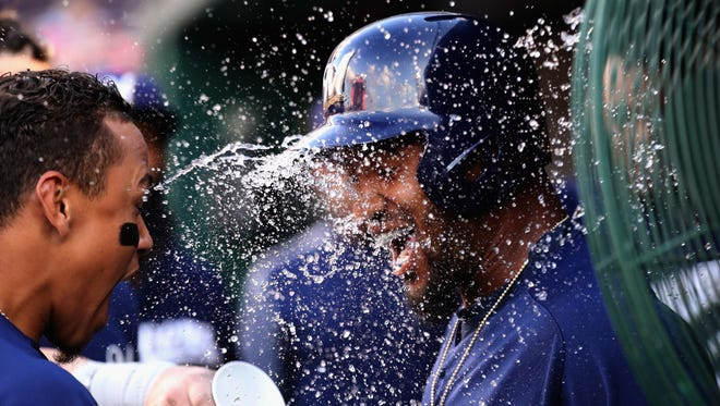 Domingo Santana gets a cup of water to the face as he celebrates his mammoth solo home run in the first inning with his Brewers teammates in the dugout on Wednesday night against the host Nationals.
