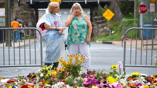 Women visit a memorial at 4th and Water Streets, Tuesday, Aug. 15 2017,  in Charlottesville, Va., where Heather Heyer was killed when a car rammed into a group of counterprotesters last weekend. Alex Fields Jr., is charged with second-degree murder and other counts after authorities say he rammed his car into a crowd of counterprotesters Saturday, where a white supremacist rally took place.