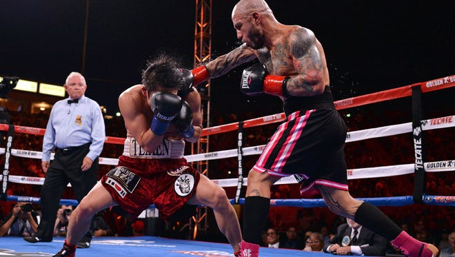 Miguel Cotto lands a right hand to the head of Yoshihiro Kamegai during their fight Saturday.