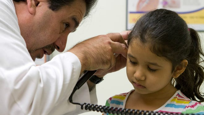 """Dr. Javier Saenz checks the ear of Viviana Escareño, 6, for infection. The young girl's mother, Claudia Escareño, has brought """"Vivi"""" to Saenz's clinic since she was born."""