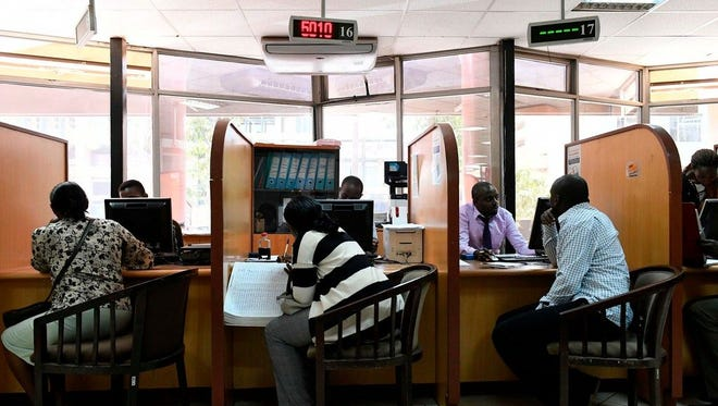 Customers speak to bank representatives at an Equity Bank branch in Nairobi, Kenya, on Feb. 6.