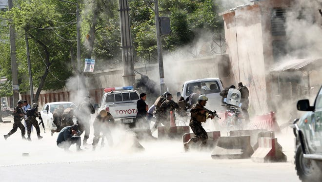 Security forces run from the site of a suicide attack after the second bombing in Kabul, Afghanistan, on April 30.