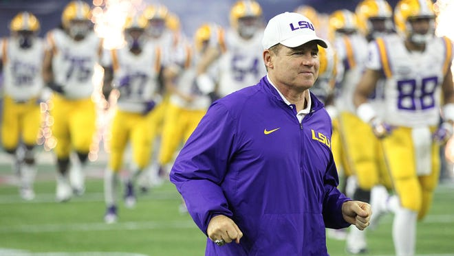 LSU Tigers head coach Les Miles and the Tigers run out on the field before playing against the Texas Tech Red Raiders at NRG Stadium. Mandatory Credit: