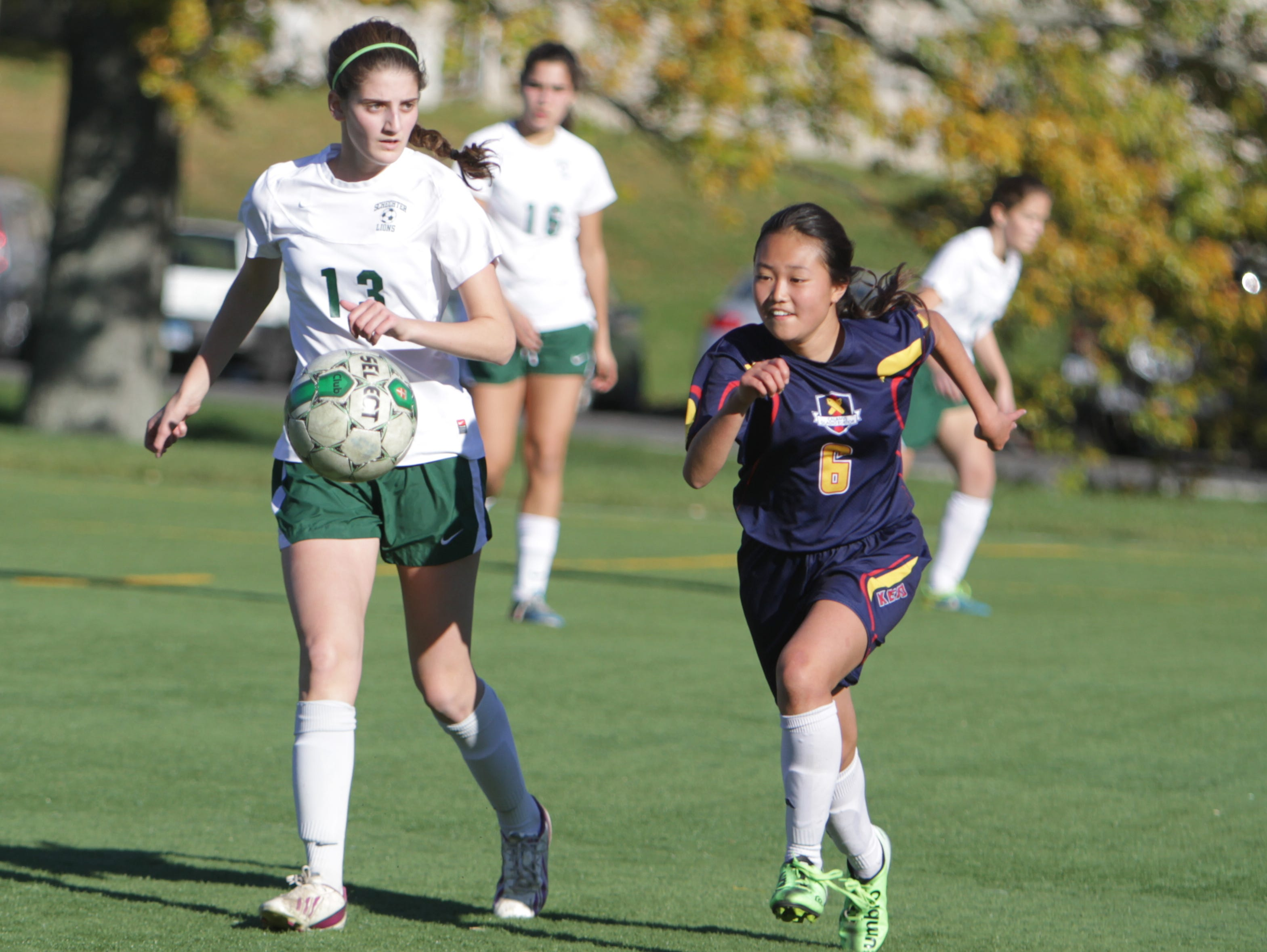 Solomon Schechter's Lulu Wein (13) and Keio's Hinako Takei chase after the ball during a Section 1, Class C quarterfinal game at Keio Academy on Monday, October 26th, 2015. Solomon Schechter won 9-2.