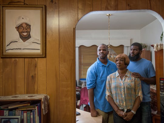 Brenda Macklin, center, and her sons Ollie Macklin, left, and Jamal Macklin, right, stand near a painted portrait of Brenda's oldest son,  Rashay Macklin, in Brenda's Camden home.  September 10th marks the 14th annivesary of the slaying of Rasay Macklin in Camden. The case is unsolved.  The 29-year-old was found shot dead in a burned out city apartment. His mother is still seeking justice.  09.05.15