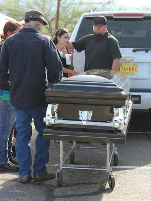Josh Barela (left) stands by the casket carrying his father, Al Barela.