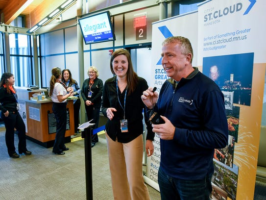 St. Cloud Mayor Dave Kleis and Michelle Whaley, public relations specialist for Allegiant Air, greet the first passengers to board the first flight to Punta Gorda, Florida, on Wednesday, Nov. 15, at the St. Cloud Regional Airport.