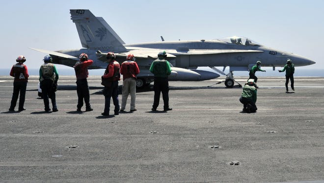 Sailors make final inspections on an F/A-18C Hornet that participated in airstrikes on militants in Iraq.