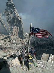 Three New York City firefighters raise the American