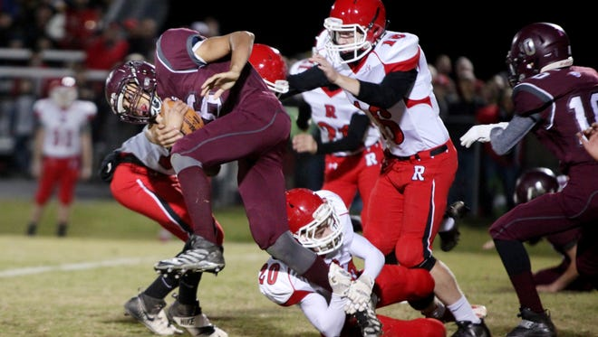 Stuarts Draft's Xzavier Gunn is tackled by Riverheads' Jason Ham, right, and Jackson Shover, bottom, during the second quarter of the game on Friday, Nov. 4, 2016 in Stuarts Draft.