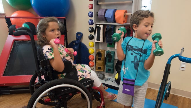 Madison Villegas, left, and her brother, Lucas, try out the equipment in the physical therapy room at the new Sacred Heart Pediatric Care Center in Gulf Breeze on Friday, July 14, 2017.