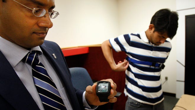 October 1, 2014 - Dr. Santosh Kumar displays a wrist sensor used to gather data from volunteers in health related studies.  The University of Memphis has been named to the Mobile Sensor Data-to-Knowledge (MD2K) team.  The team will develop tools and methods to more easily gather, analyze and interpret health-related data collected from wearable and mobile sensors.  The sensors were designed and developed by Dr. Emre Ertin at the University of Ohio. (Stan Carroll/The Commercial Appeal)