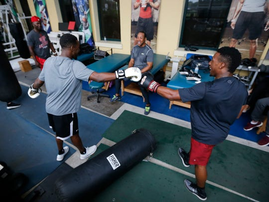 MLB prospects Nick Gordon (left) and Shed Long (right) bump fists as Hall of Famer Barry Larkin laughs after Long punches the heavy bag out of its fixture in the rafters during a workout at the ESPN Wide World of Sports Complex in Orlando, Fla., on Friday, Dec. 8, 2017.
