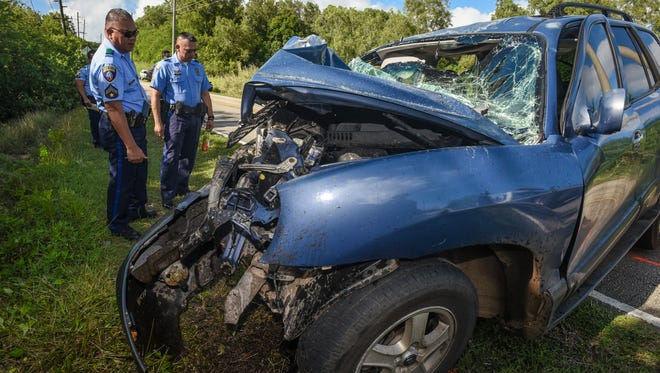 Officer J.L. Laxamana, left, and other Guam Police officers conduct an investigation of an auto-pole collision involving a Hyundai Santa Fe vehicle on Route 4A on Jan. 4, 2017.