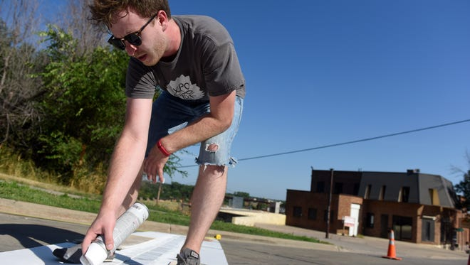 Zach DeBoer paint parking stripes for reverse diagonal parking along North Main Avenue on Wednesday.