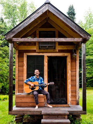 Ethan Walden, 31, is pictured on the front porch of his Morrisville tiny home he built in 2012.