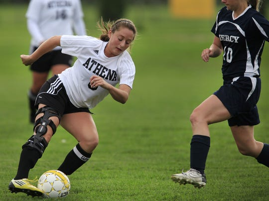 Greece Athena's Brooke Testa , left, in action against Mercy in 2013.