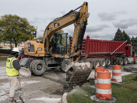 Road construction crews remove old roadway and curbs before replacing the road surface.