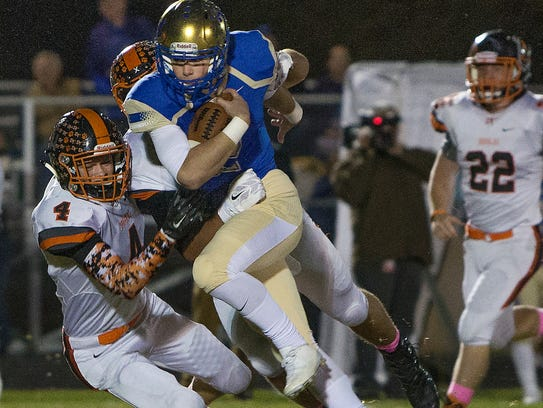 Reed quarterback Cameron Emerson is grabbed by Douglas