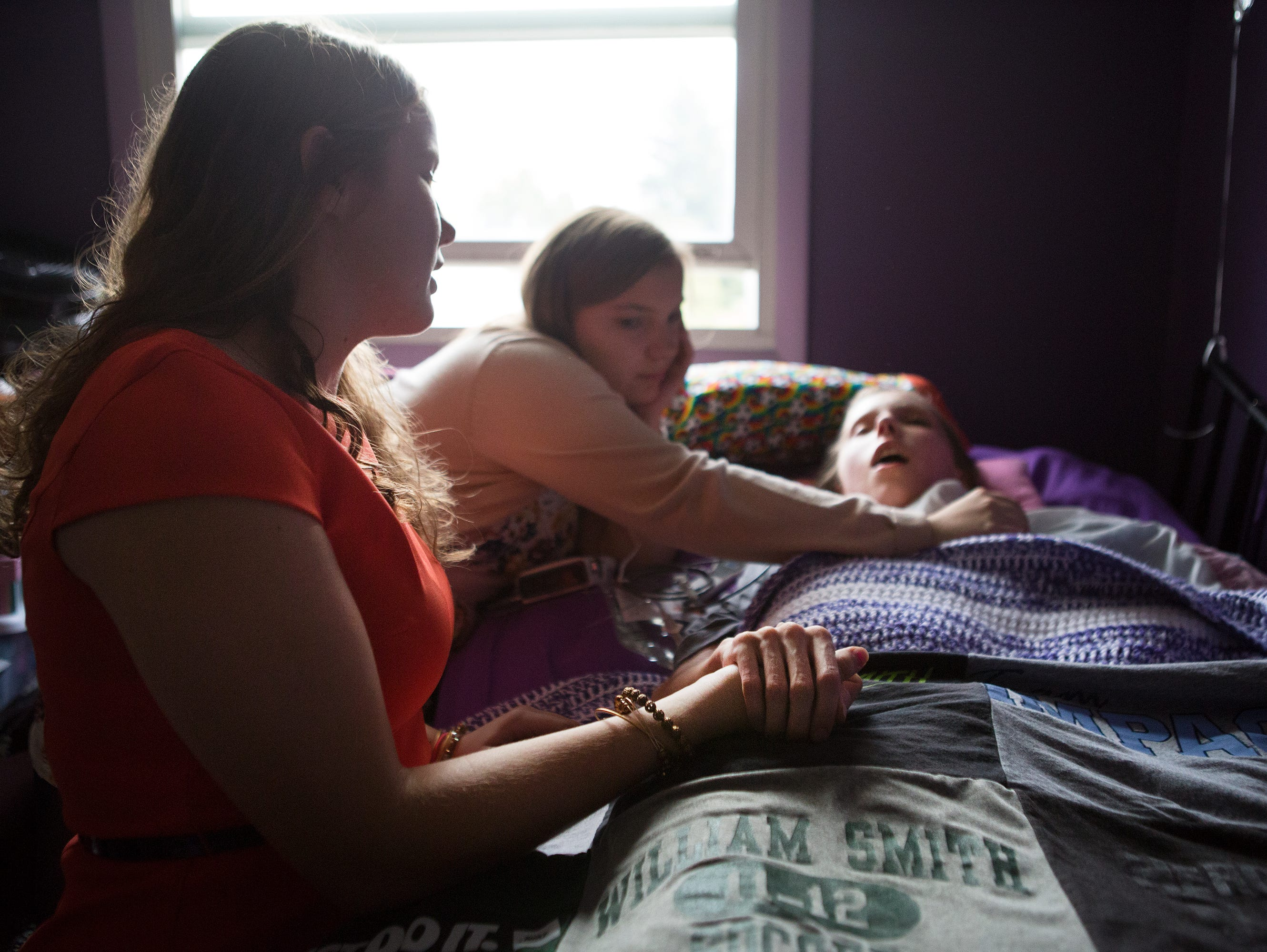 Courtney Wagner is comforted by her 17-year-old twin sisters, Allie and Alex, in their home in Farmington on Wednesday, October 21, 2015. Their mom says the twins have been doing their homework in her room every night.