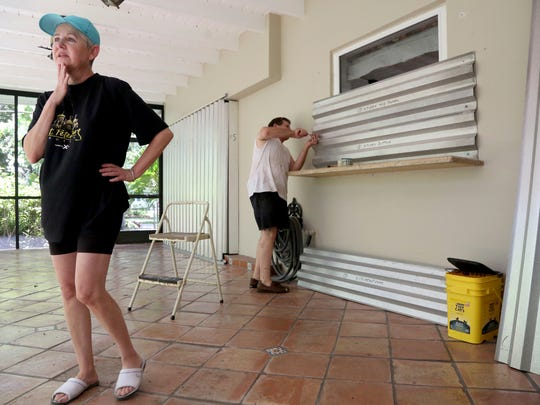 Yvette Sedeno, 62, left, and Ray Sedeno, 62, install storm shutters on to their windows on their lanai while preparing for the arrival of Hurricane Irma on Friday, Sept. 8, 2017, in unincorporated Dade County, south of Miami.