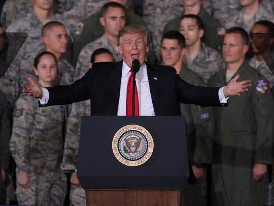 El presidente Donald Trump habla frente a elementos