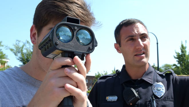 City of Franklin Police Teen Academy participant Zane Lockwood, 15, learns how to use a hand-held radar to track the speed of passing cars with the help of Franklin officer Mike Adcock outside the police headquarters on Wednesday, July 13, 2016.