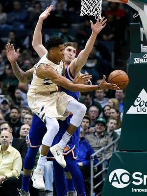 Giannis Antetokounmpo  passes the ball away from  Knicks forward Luke Kornet in the second quarter Friday night.