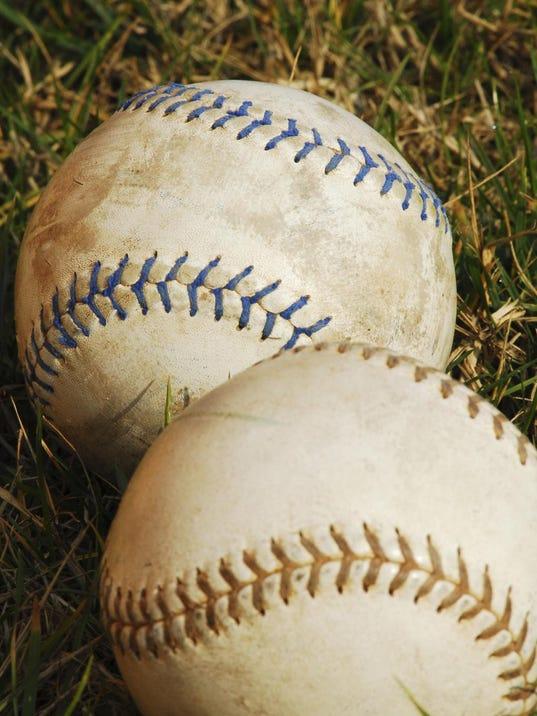 softballs in grass - vertical