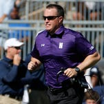 Northwestern football coach Pat Fitzgerald runs across the field against Penn State on Sept. 27, 2014.
