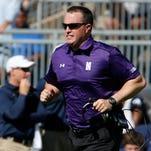Northwestern football coach Pat Fitzgerald runs across the field against Penn State on Sept. 27, 2014.