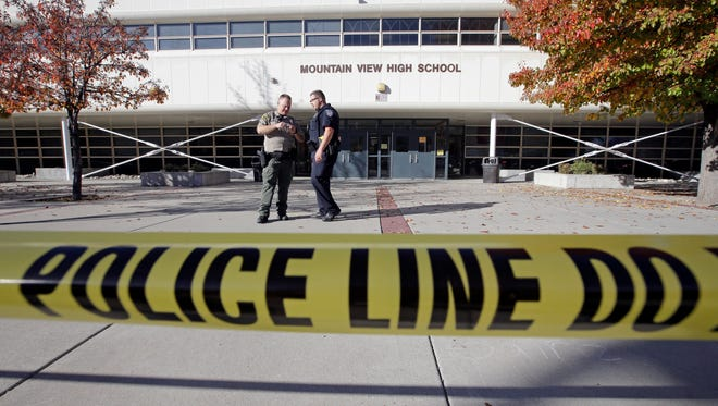 Police stand outside Mountain View High School after several students were stabbed inside the high school Tuesday, Nov. 15, 2016, in Orem, Utah Police say a 16-year-old boy was taken into custody after the stabbings.