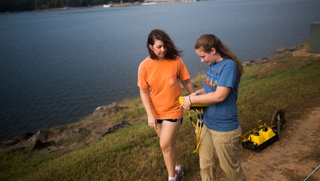 Graduate students Allison Sams (left) and Rebecca Dozier (right) use a Ground Penetrating Radar to sense the differences in structure and density of subsurface material on Clemson University's levee on Tuesday, September 27, 2016.