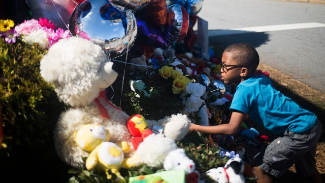 Braylon Woodruff, 5, places balloons Thursday on the memorial outside Townville Elementary School. Thursday was students' first day back to classes after last week's shooting at the campus.