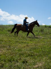 A rider walks his horse through a field during the