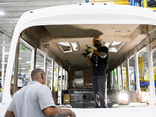 Patrick Tyler and William Ayers work on a bus at the