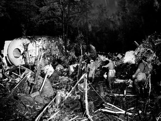 Firefighters clear debris from around the wreckage of a military air transport plane that crashed seconds after takeoff from McGuire Air Force Base near Fort Dix, N.J., on July 13, 1956. Personnel at left check a section of the fuselage for clues to the cause of the crash, which killed 45 people and injured 21. The plane was bound for England.