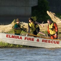 Firefighters take part in a 2011 rescue operation on the Chemung River in Elmira.