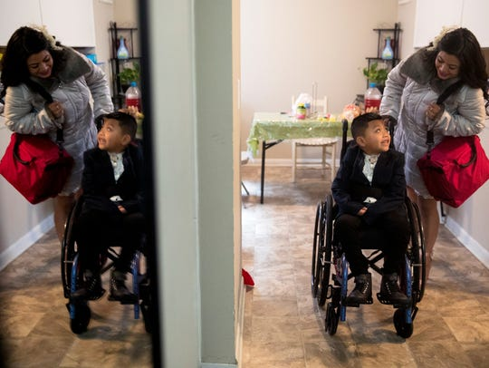 Sandra Mendoza pushes Ricky's wheelchair to leave their