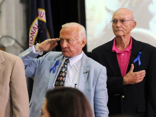 Astronauts Jim Lovell, Buzz Aldrin and Michael Collins stand for the National Anthem during a ceremony Monday, July 21, 2014 renaming the Operations and Checkout Building at Kennedy Space Center, FL for astronaut Neil Armstrong.  The iconic building houses astronaut crew quarters and also where the new Orion capsule is being developed.