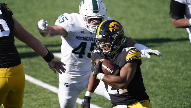 Iowa running back Ivory Kelly-Martin runs from Michigan State linebacker Noah Harvey, rear, during the first half of Saturday's game, in Iowa City, Iowa.
