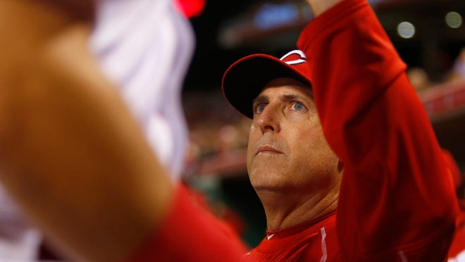 Cincinnati Reds manager Bryan Price congratulates players in the dugout during the sixth inning against the Chicago Cubs at Great American Ball Park. The Reds won 13-5.