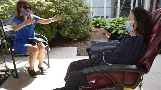 Marcie Abramson, left, gestures as she speaks to her mother, Cynthia, outdoors at the Hebrew Rehabilitation Center on Wednesdayin Boston, under the state's new nursing home visitation guidelines which requires social distancing. The two haven't been able to visit in person since March.