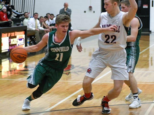 Pennfield's Grant Petersen (21) drives the court during second quarter of play Friday night.