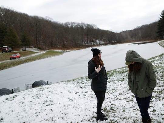 Sally Sugar, 23, an Ohio Stream Restore Corps AmeriCorps member, left, tours Tecumseh Lake, a 13-acre artificial lake constructed in 1952 to serve as a recreation area for residents, alongside Selina Nadeau, 22, an AmeriCorps member with with Ohio's Hill County Heritage Area group, Thursday, Dec. 14, 2017, in Shawnee, Ohio. Communities across Appalachia are turning increasingly to the region's rich reserves in things other than coal, namely, history and rugged natural beauty, to frame a new tourist economy. Enjoying a drink, hike or overnight stay or in region infused with stories, sweat and strife is turning out to be a draw to aging baby boomers and millennials alike. (AP Photo/John Minchillo)